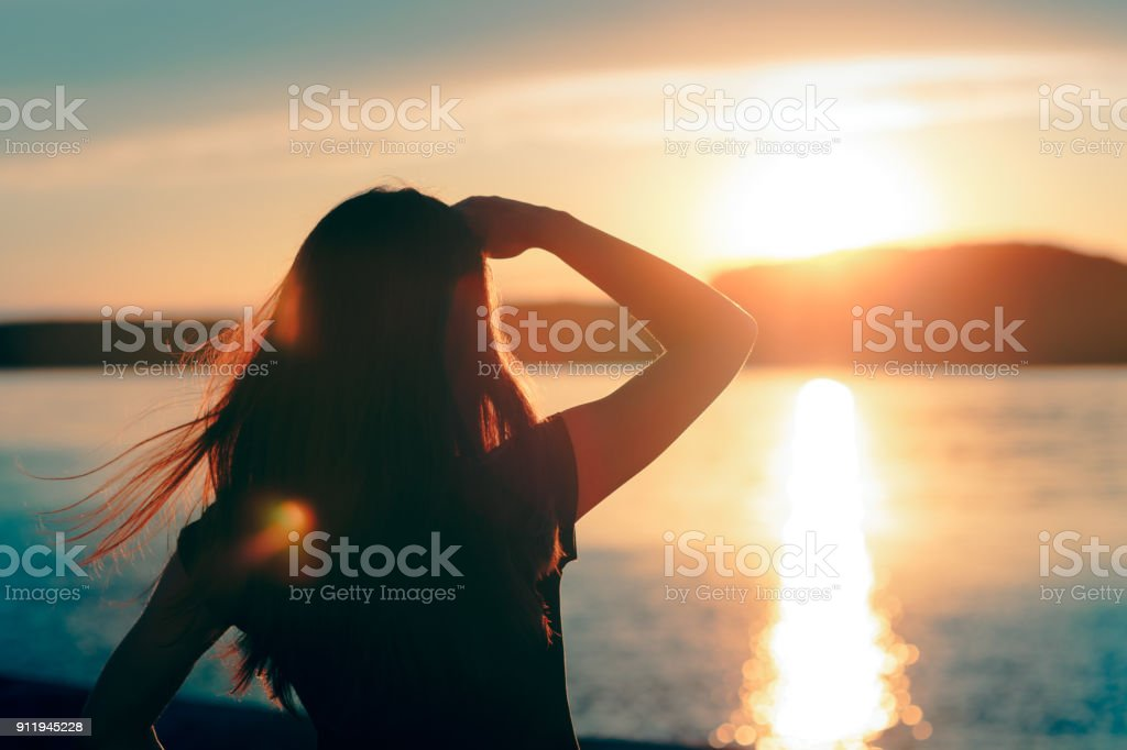 Happy Hopeful Woman Looking at the Sunset by the Sea stock photo