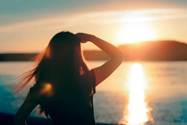 glad hoppfull kvinna som tittar på solnedgången vid havet - horisont bildbanksfoton och bilder