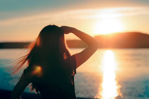 happy hopeful woman looking at the sunset by the sea - vitamin d стоковые фото и изображения