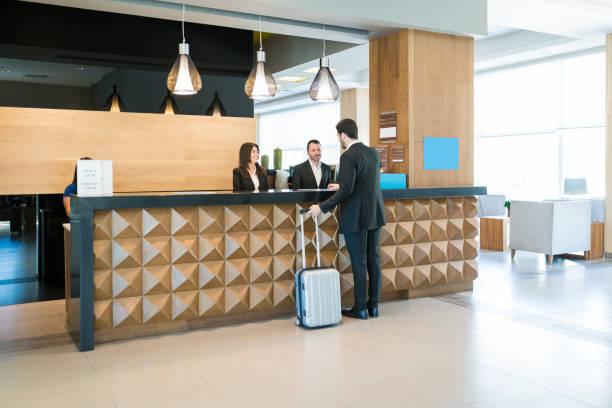 happy hotel clerks wita profesjonalnych w kasie - hotel zdjęcia i obrazy z banku zdjęć