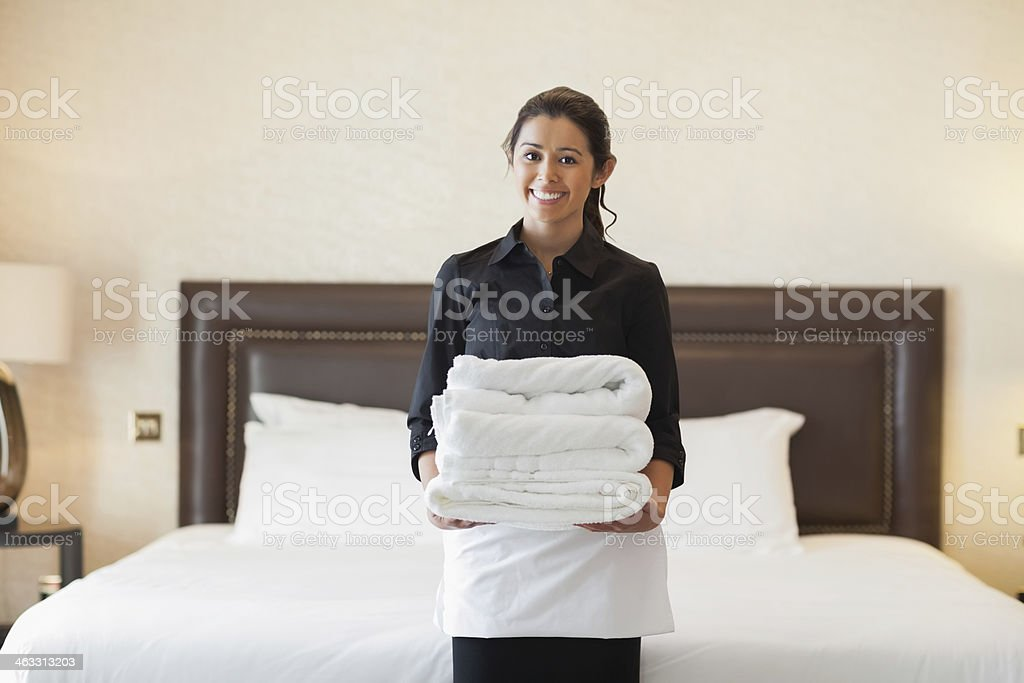 Happy hotel maid holding towels stock photo