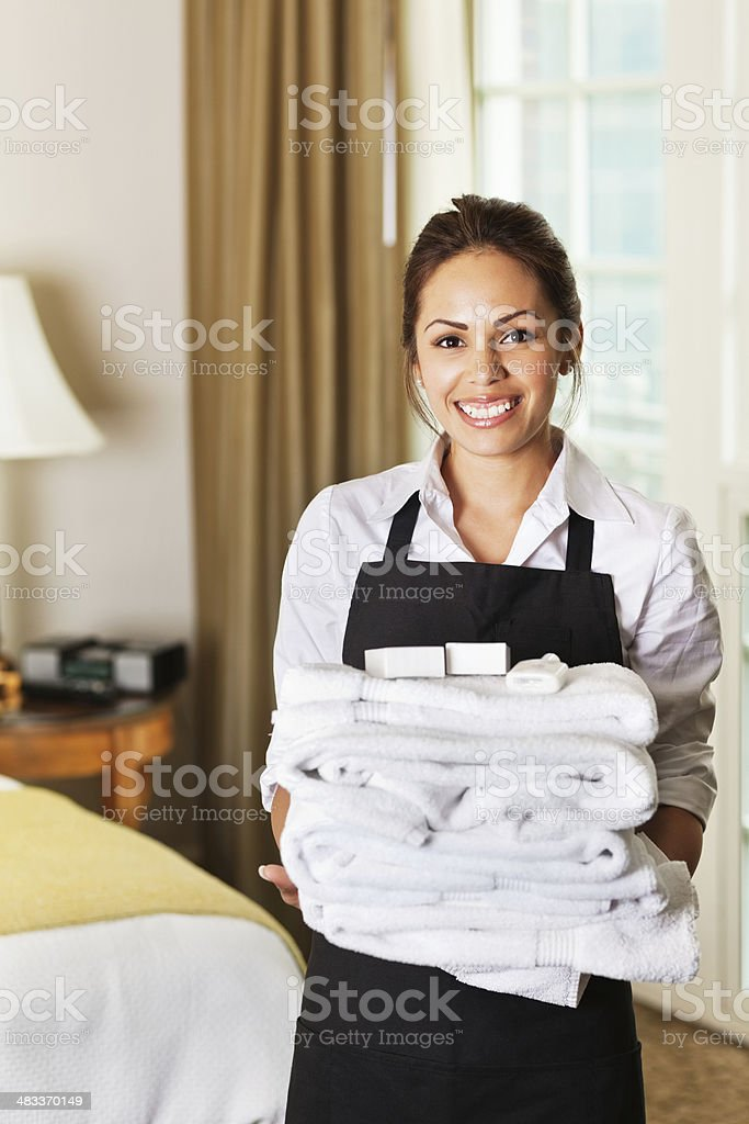 Happy hotel maid with towels in a guest room stock photo