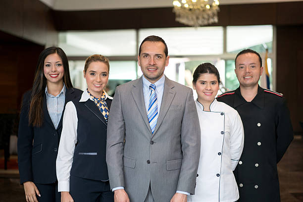 happy hotel staff - uniform stock photos and pictures