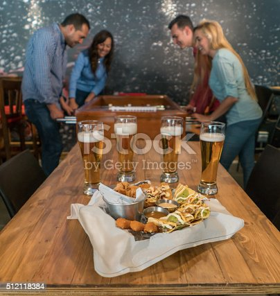 Group of friends enjoying the happy hour at the bar drinking beer, eating snacks and playing foosball