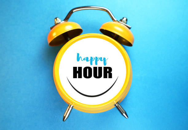 Happy hour concept. Alarm clock smiling and text. stock photo