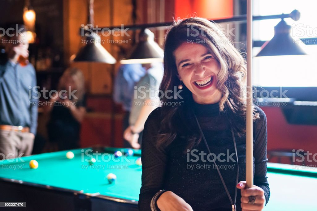 Happy hour for friends and coworkers in a bar playing pool. stock photo