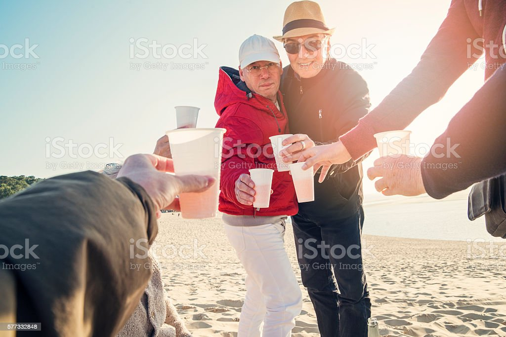 Happy hour for group of friends on beach in spring. – Foto