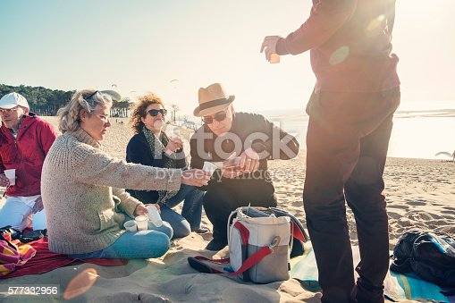 Happy hour for group of friends on the beach in spring. Three man and two woman, different ages, all wearing warm clothes, holding their plastic glasses to be filled with some sparkling rose wine. Horizontal shot with sun flare. This was taken at the Dune du Pilat, France.