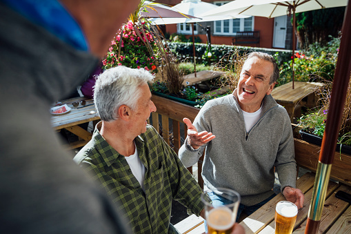 Over the shoulder view of male friends sitting and standing around a wooden table in a beer garden in Polperro, Cornwall. They are drinking beers and having a laugh.