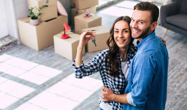 glückliche einweihungsparty. ein junges paar hält glücklich einen schlüssel zu ihrem neuen zuhause, das sie so aufgeregt waren, und das kann nicht anders, als sie fühlen sich mit positiven emotionen überwältigt. - lifestyle stock-fotos und bilder