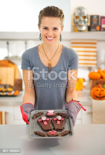 Happy modern housewife in decorated kitchen showing off freshly baked Halloween biscuits for Trick or Treat. Ready to halloween party. Traditional autumn holiday