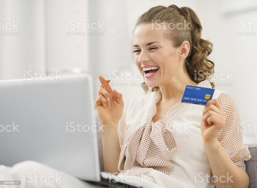 happy housewife with laptop and credit card crossed fingers stock