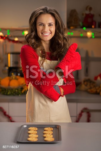 istock Happy housewife with pan of fresh cookies showing thumbs up 527116237