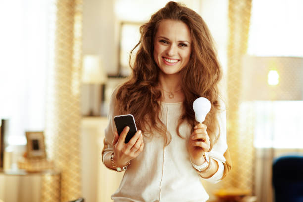 Glückliche Hausfrau mit Smartphone und Smart Lampe im modernen Haus – Foto