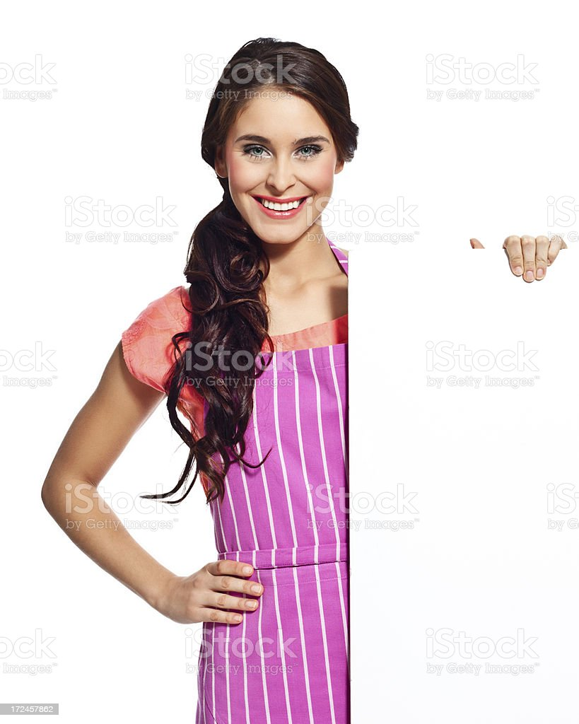 Happy housewife with whiteboard Portrait of happy young woman wearing an apron holding a whiteboard and smiling at the camera. 20-24 Years Stock Photo