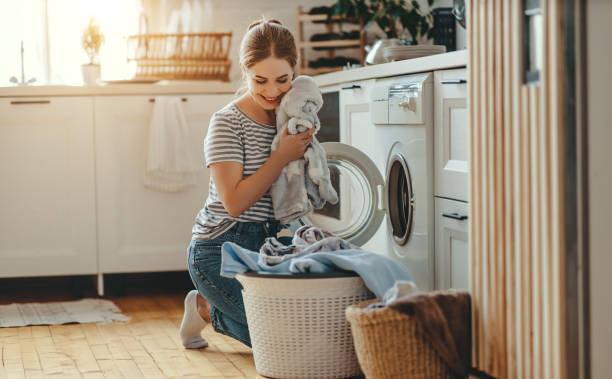 Glückliche Hausfrau Frau in Waschküche mit Waschmaschine – Foto
