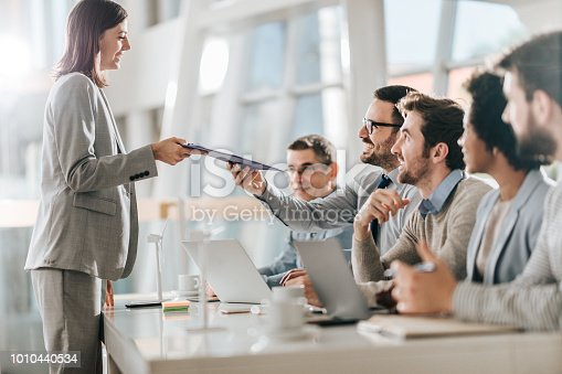 Happy female candidate talking to human resource team while giving them application form on a job interview in the office.