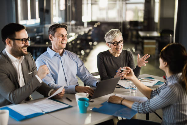 Happy human resource team talking to female candidate on a job interview. stock photo