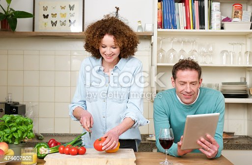 638771390istockphoto Happy husband and wife cooking in the kitchen 474607502