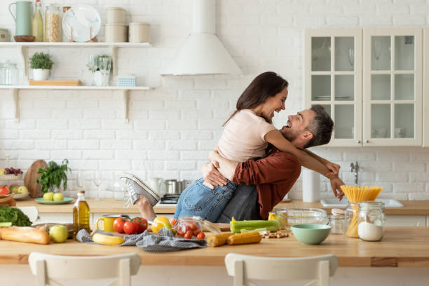 Happy husband and wife having fun during cooking stock photo