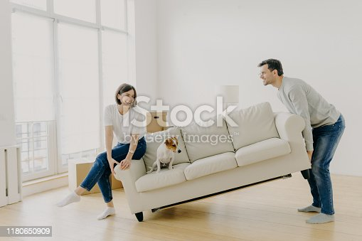 istock Happy husband and wife place sofa in living room, furnish their first home, help each other in renovation, little dog sits on couch, carry furniture together. Remodeling and renovation concept 1180650909
