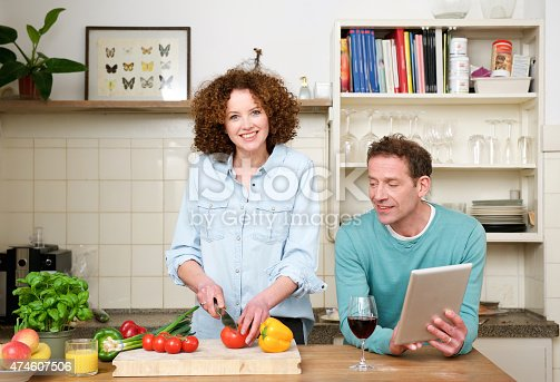 638771390istockphoto Happy husband and wife together in the kitchen 474607506