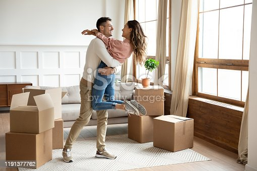 Happy young husband lifting excited wife celebrating moving day with cardboard boxes, proud overjoyed family couple first time home buyers renters owners having fun enjoy relocation, mortgage concept