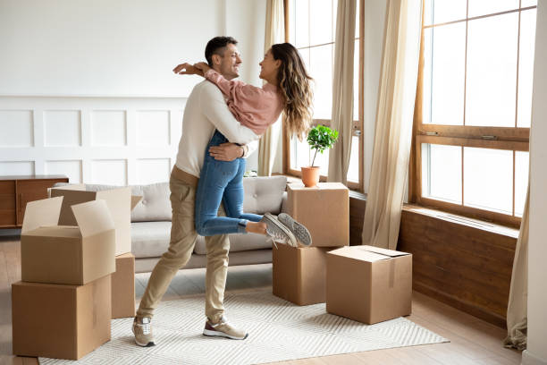 Happy husband lifting excited wife celebrating moving day with boxes Happy young husband lifting excited wife celebrating moving day with cardboard boxes, proud overjoyed family couple first time home buyers renters owners having fun enjoy relocation, mortgage concept two parents stock pictures, royalty-free photos & images