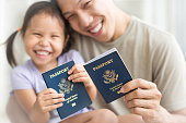 Asian dad and daughter holding amercian passports with pride. Immigration citizenship