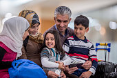 A Middle-eastern father, mother, brother and two sisters have just arrived to a new country. They are happily sitting together and smiling. The father is holding his family's passports. Their luggage is sitting to the side.