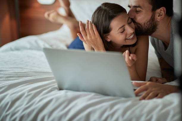 Happy in bed – couple enjoying and kissing in the bed stock photo