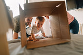 Photo of a young family with a little boy, being happy and excited about moving into a new home