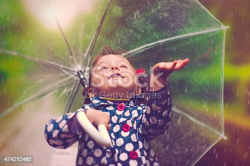 Little girl happily catching drops of rain