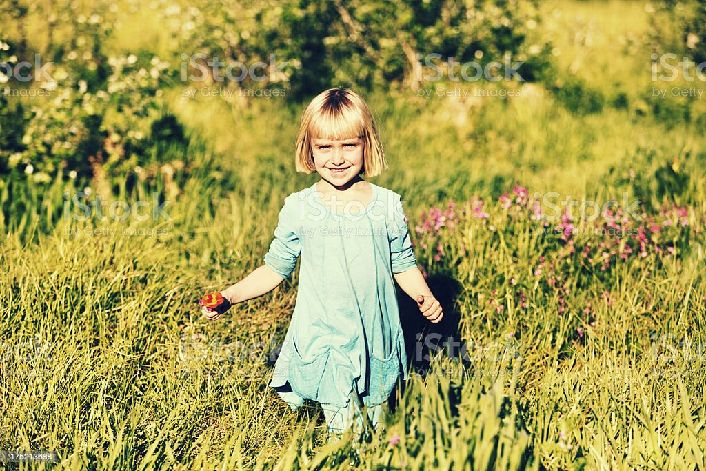 Happy in springtime! Little girl running through meadow stock photo