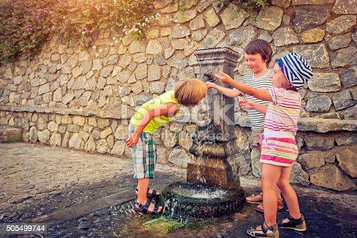 Three happy children having fun with a fountain un summer heat