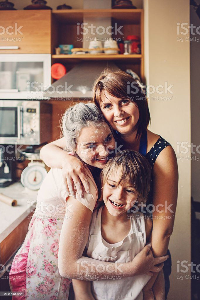 Mother holding her children in the kitchen, all are smiling and...
