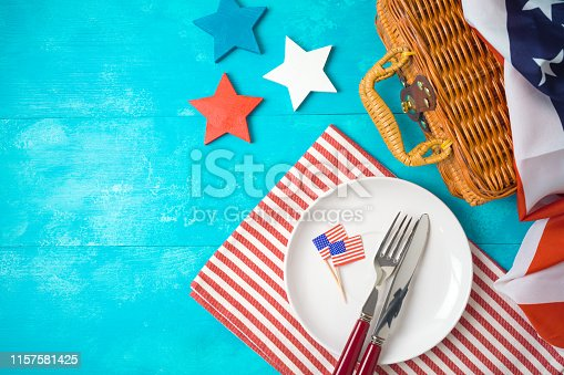 Happy Independence Day, 4th of July celebration concept with picnic basket, plate and USA flag on wooden background. Top view from above