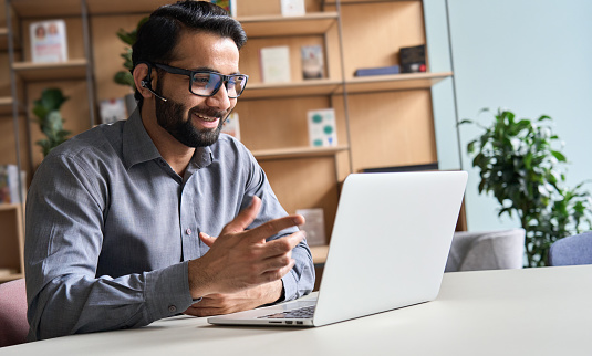 Happy indian business man remote teacher, customer support manager wearing headset talking at virtual meeting consulting client on video call giving distance learning class at home office call center.