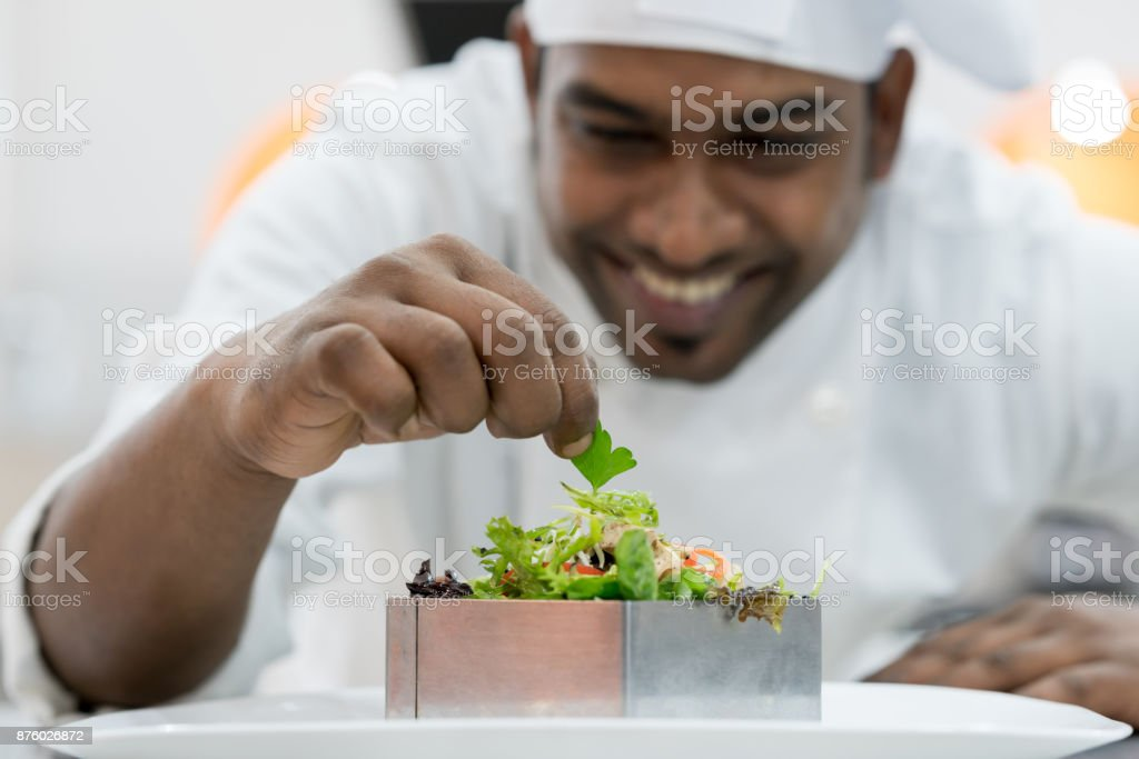 Happy indian chef adding details to his finished plate stock photo