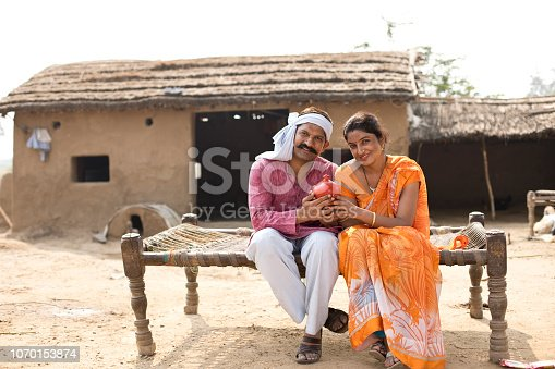 Happy Indian couple holding piggy bank while sitting on traditional bed at village
