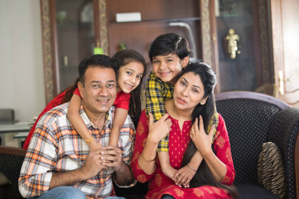 Happy Indian family Happy Indian family sitting on sofa in the living room indian family stock pictures, royalty-free photos & images