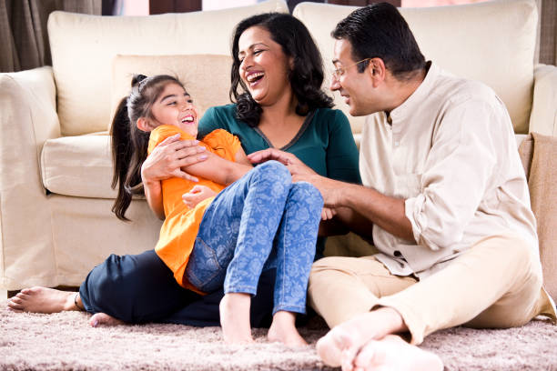 Happy Indian family Happy parents spending leisure time with daughter at home indian family stock pictures, royalty-free photos & images