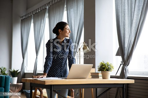 Overjoyed millennial Indian girl stand at wooden desk in living room work on laptop gadget look in distance thinking, happy young ethnic woman distracted from computer job dreaming or visualizing