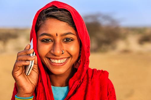 Happy Indian girl using mobile phone in desert village, Thar Desert, Rajasthan, India.