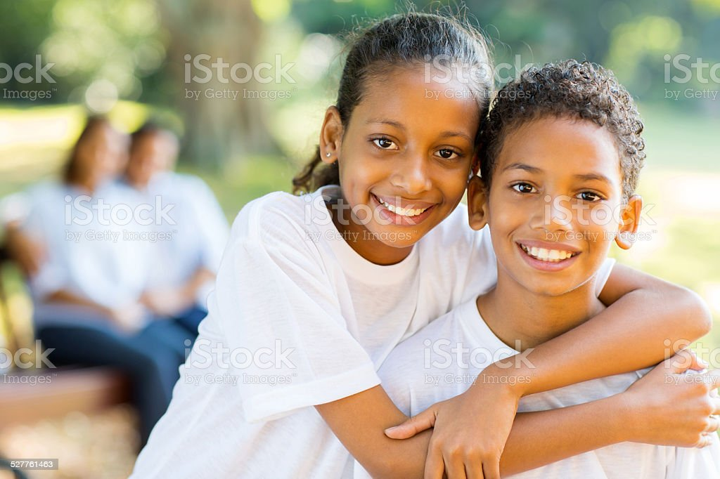 happy indian sister and brother standing in front of parents stock photo
