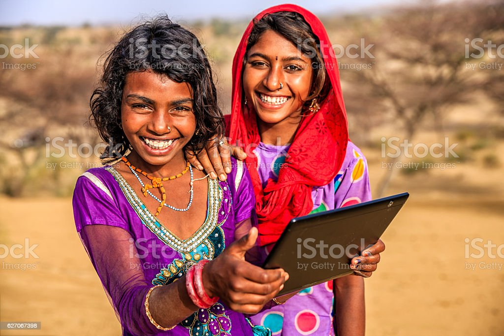 Happy Indian young girls using digital tablet, desert village, India stock photo
