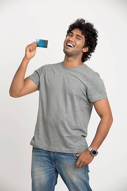 happy Indian young man showing credit card stock photo