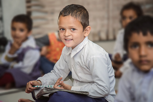 Happy Indian/Asian poor village school boy sitting in classroom. looking at camera