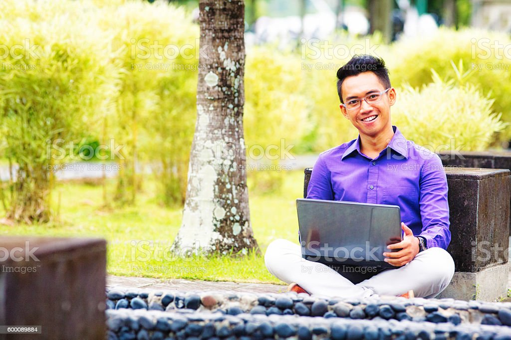 Happy Indonesian male student outdoors portrait with laptop stock photo
