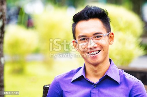 istock Happy Indonesian male student portrait with braces and glasses 605997798